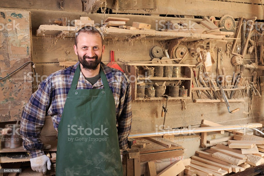 Portrait of male carpenter worker posing at his workshop stock photo