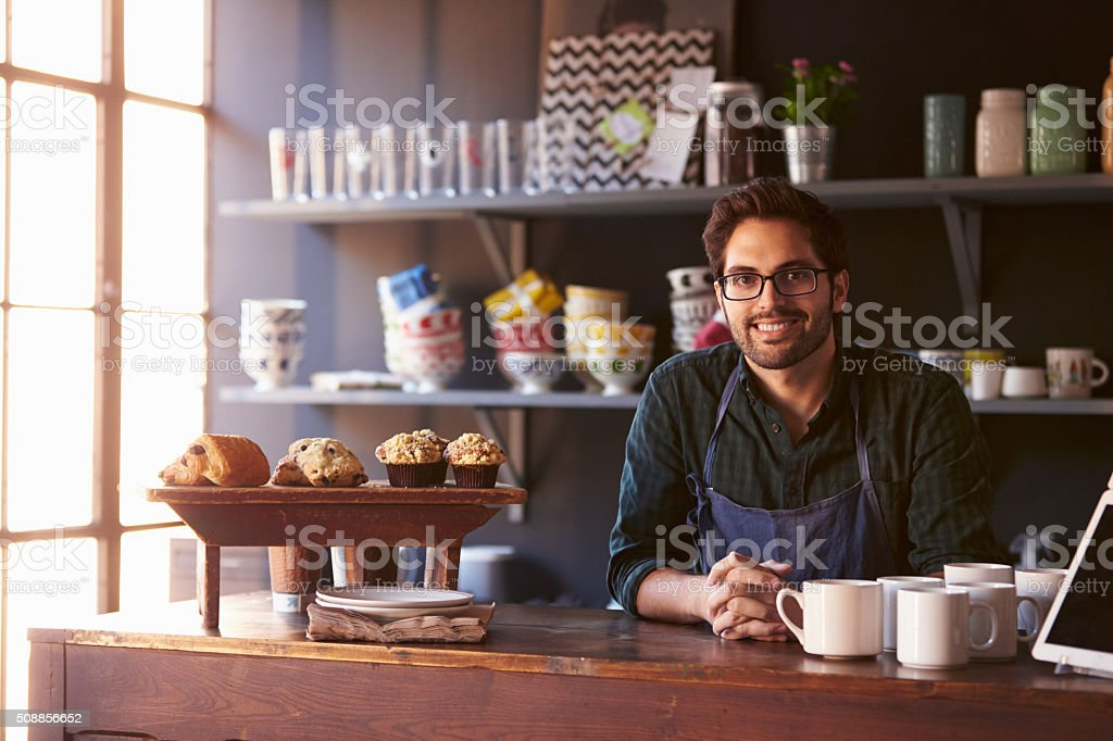 Portrait Of Male Coffee Shop Owner Standing Behind Counter stock photo