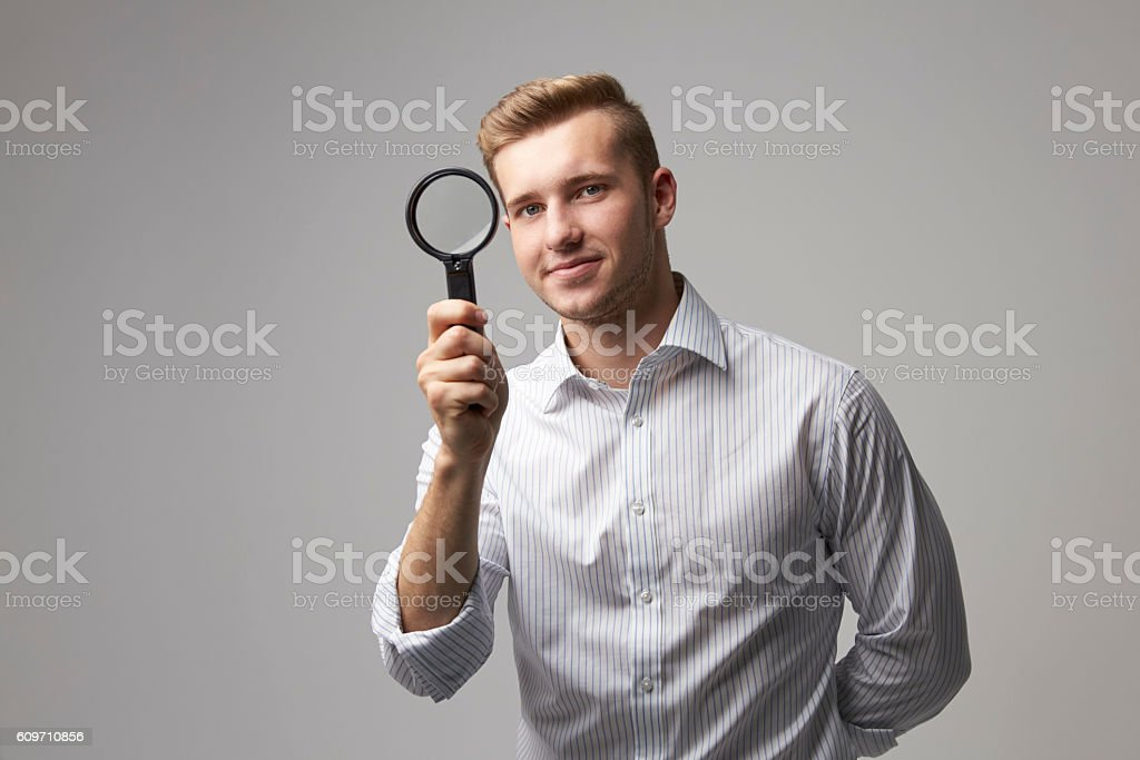 Portrait Of Male Criminologist With Magnifying Glass stock photo