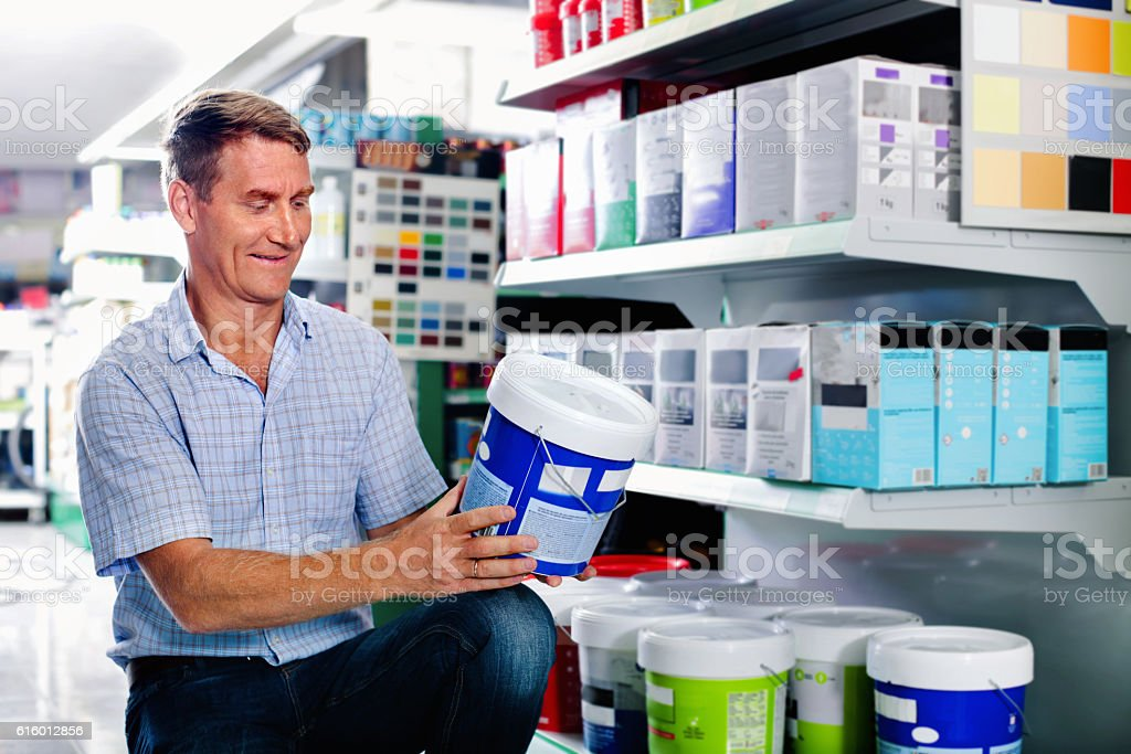 Portrait of male customer selecting paint can in housewares depa stock photo