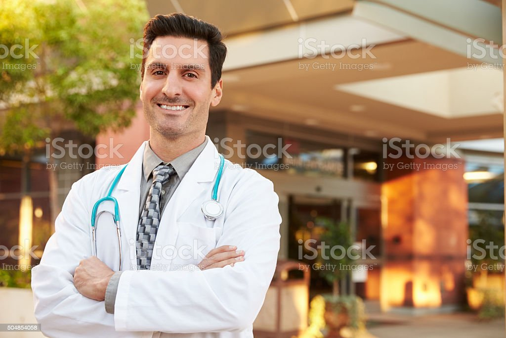 Portrait Of Male Doctor Standing Outside Hospital stock photo