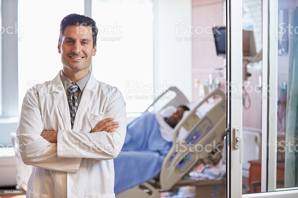 Portrait Of Male Doctor With Patient In Background stock photo