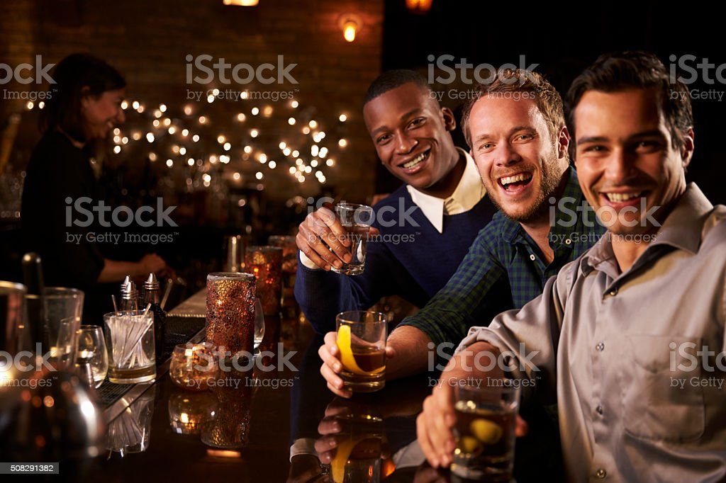 Portrait Of Male Friends Enjoying Night Out At Cocktail Bar stock photo