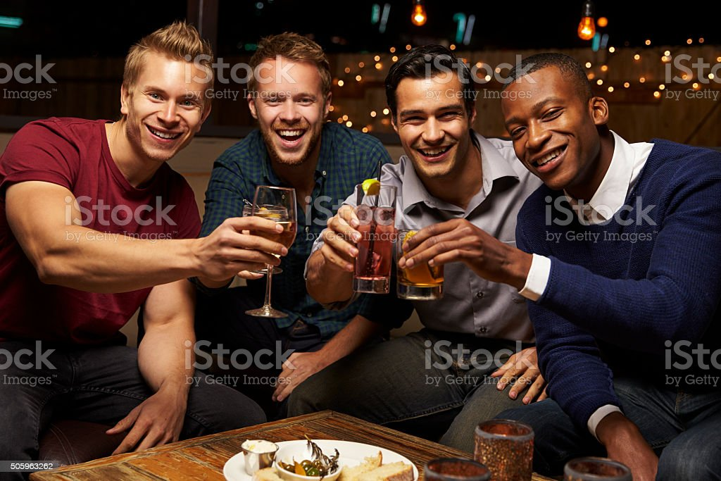 Portrait Of Male Friends Enjoying Night Out At Rooftop Bar stock photo