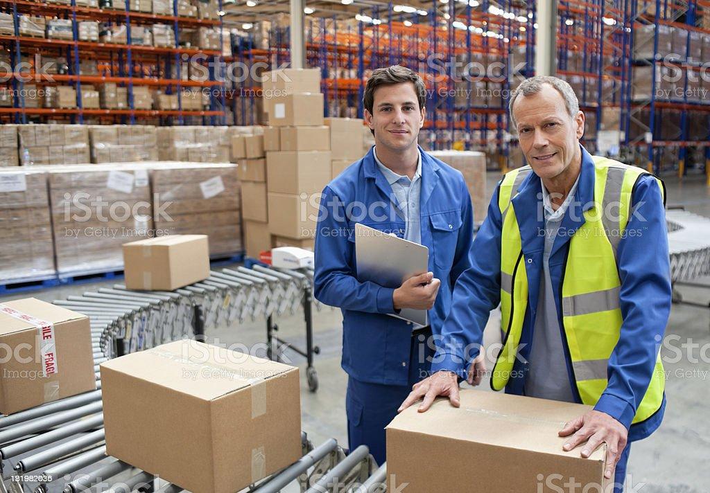 Portrait of male warehouse workers near conveyor belt stock photo