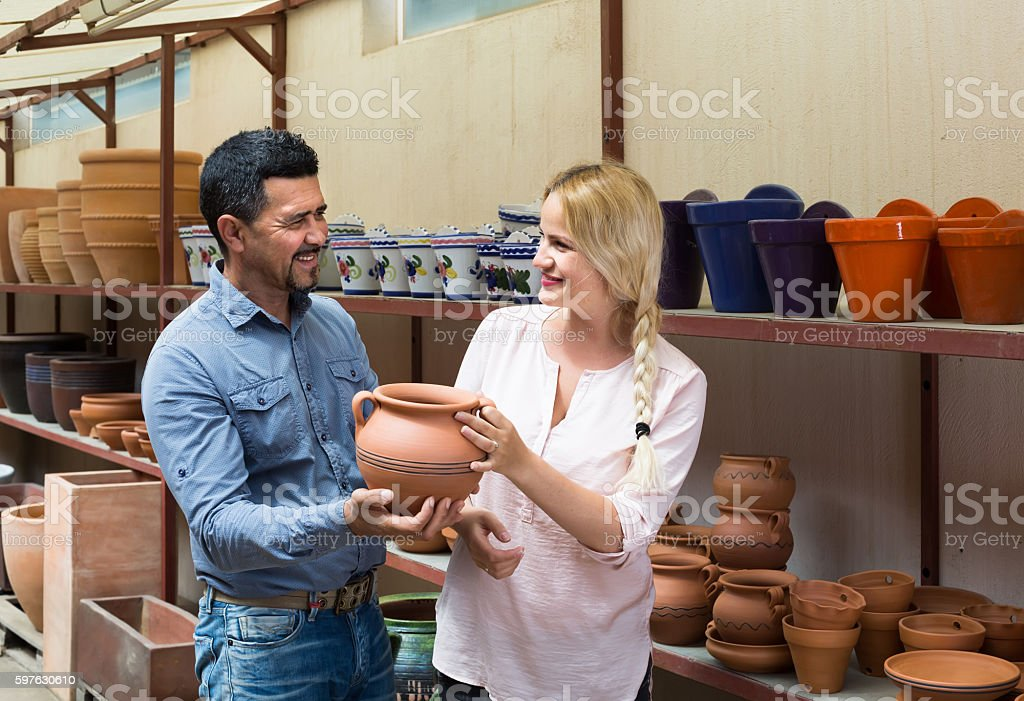 portrait of man and woman shopping ceramic utensil in boutique stock photo