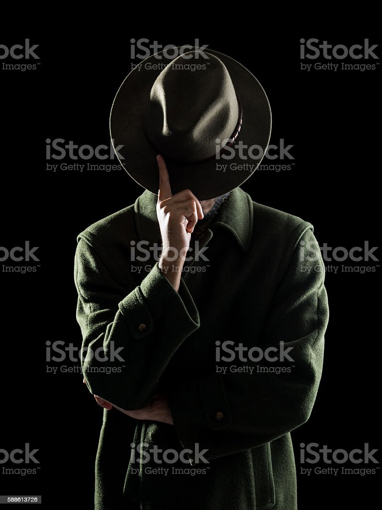 Portrait Of Man Hiding His Face With Fedora Hat stock photo