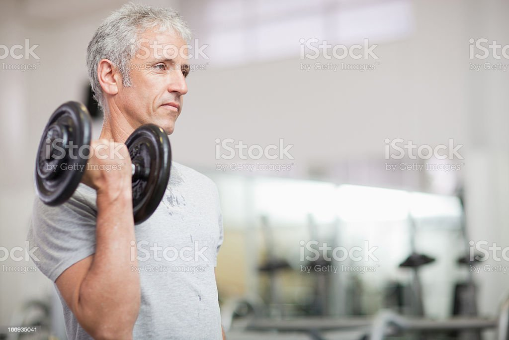Portrait of man holding barbell in gymnasium royalty-free stock photo