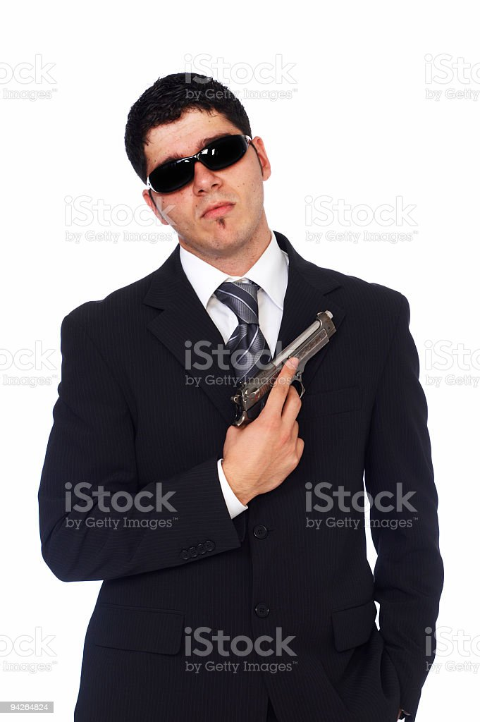 Portrait of man holding gun wearing black suit and sunglasses royalty-free stock photo