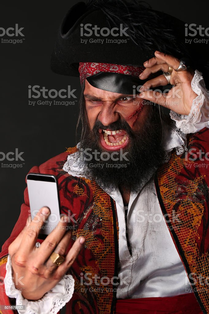 Portrait of man in a pirate costume with mobile phone stock photo