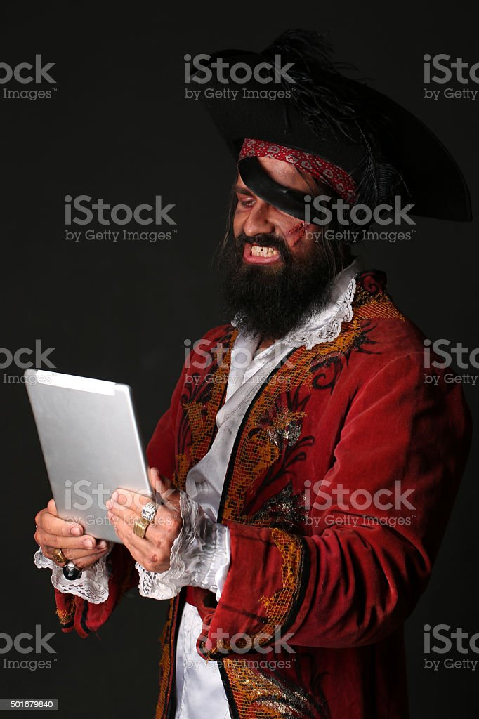 Portrait of man in a pirate costume with tablet stock photo
