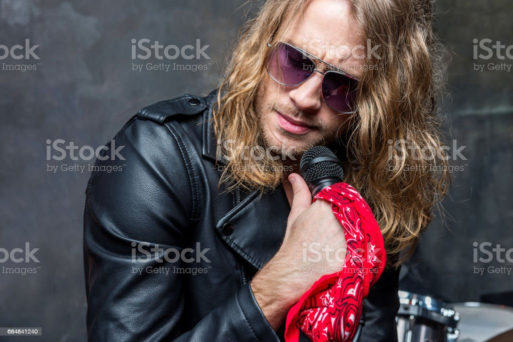 portrait of man in glasses holding microphone, male singer with microphone concept stock photo