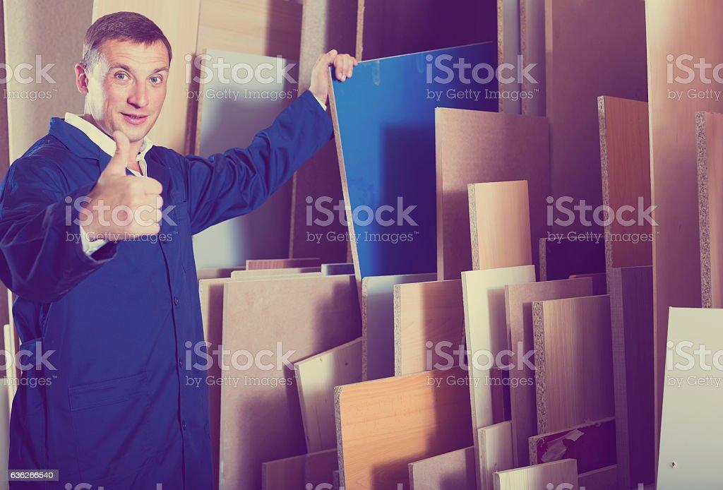 portrait of man in uniform choosing compressed densified wood in stock photo