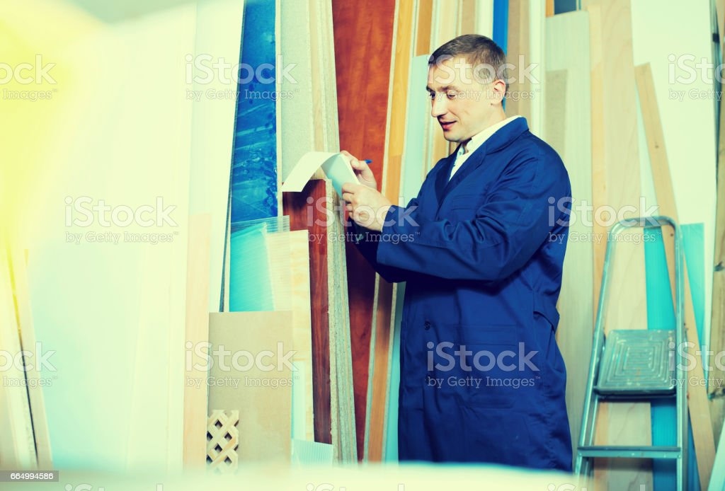 portrait of man in uniform choosing compressed densified wood in picture framing atelier stock photo