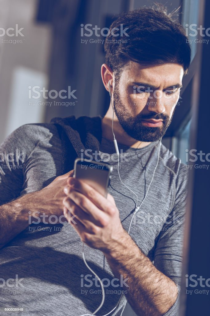 portrait of man listening music in earphones after training stock photo