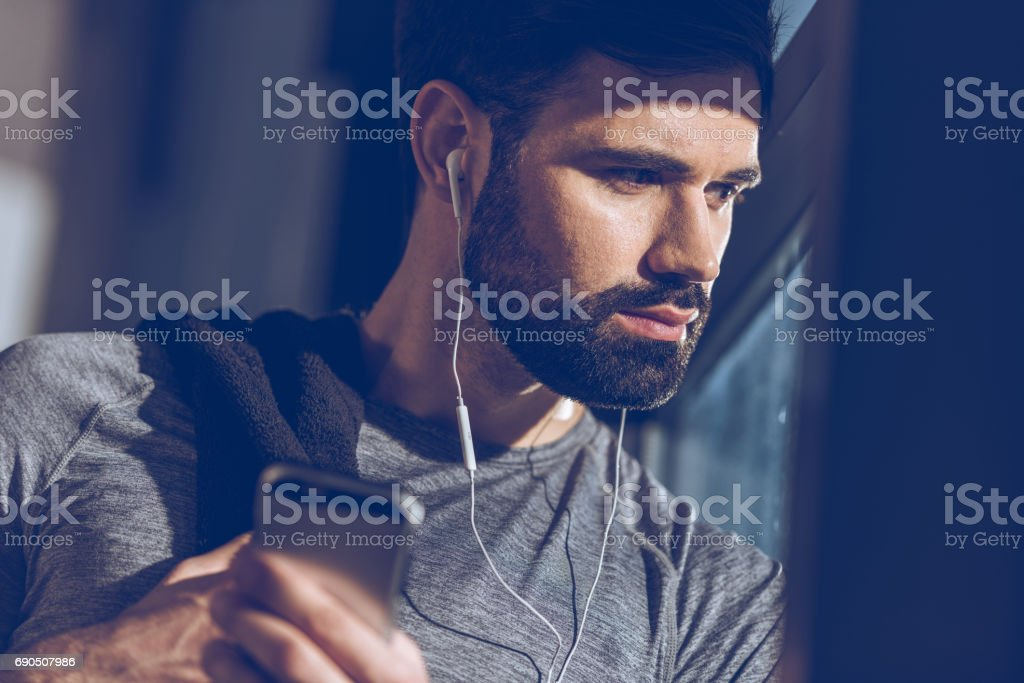 portrait of man listening music in earphones and looking out window stock photo