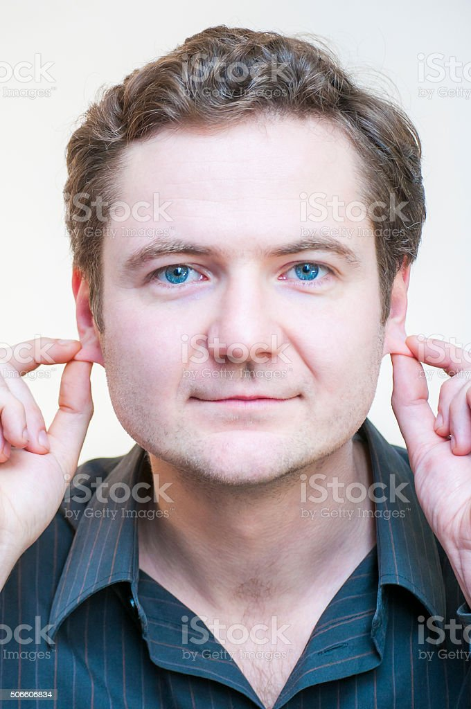 Portrait of man points on his ears. Human face parts. stock photo