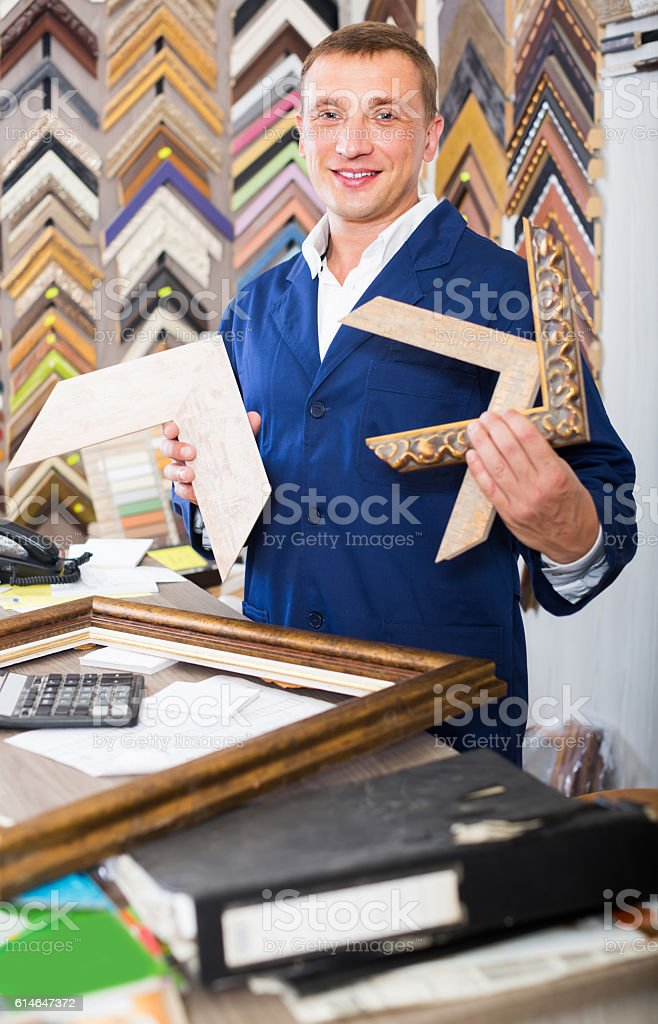 portrait of man seller working with picture frames in atelier stock photo