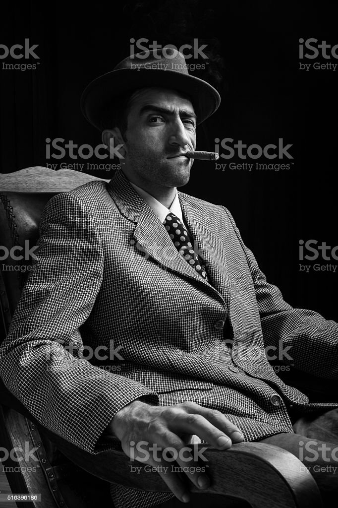 Portrait Of Man Sitting On Armchair And Smoking Cigar stock photo