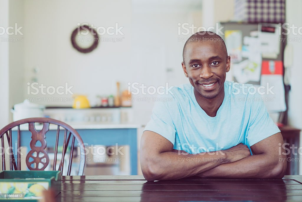 Portrait of man smiling at table in kitchen stock photo