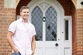 Portrait Of Man Standing Outside Front Door Of Home