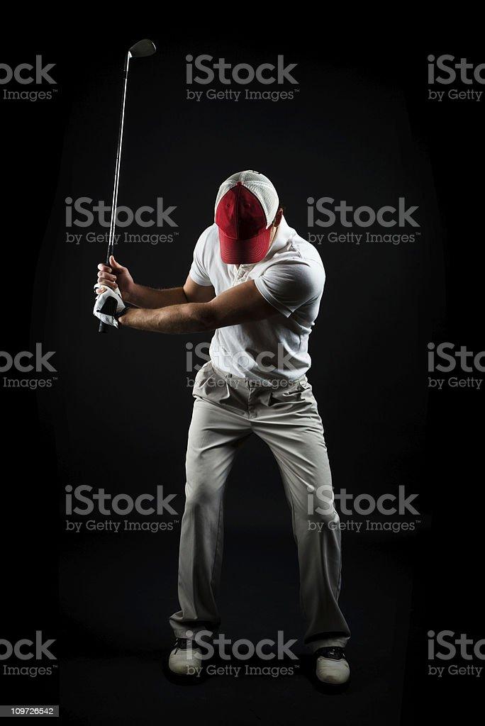Portrait of Man Swinging Golf Club, Isolated on Black royalty-free stock photo