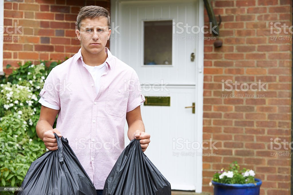 Portrait Of Man Taking Out Garbage In Bags stock photo