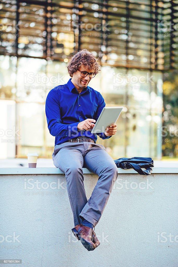 Portrait of man using digital tablet on public wi-fi spot stock photo
