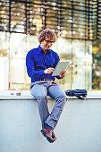 Portrait of man using digital tablet on public wi-fi spot