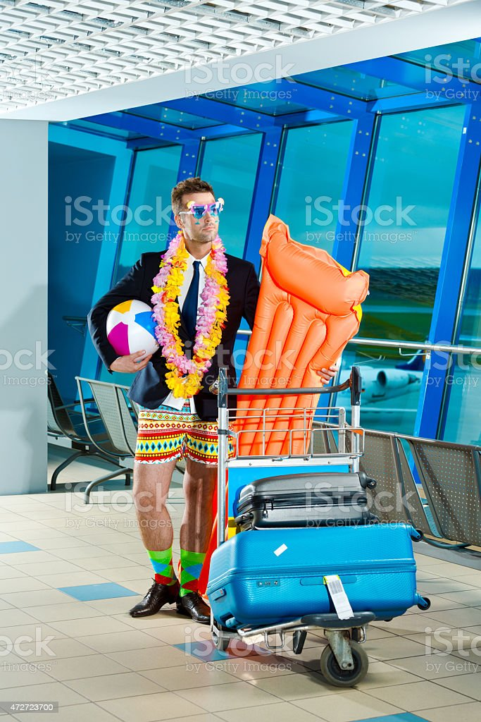 Portrait of man wearing beach short and jacket at airport stock photo