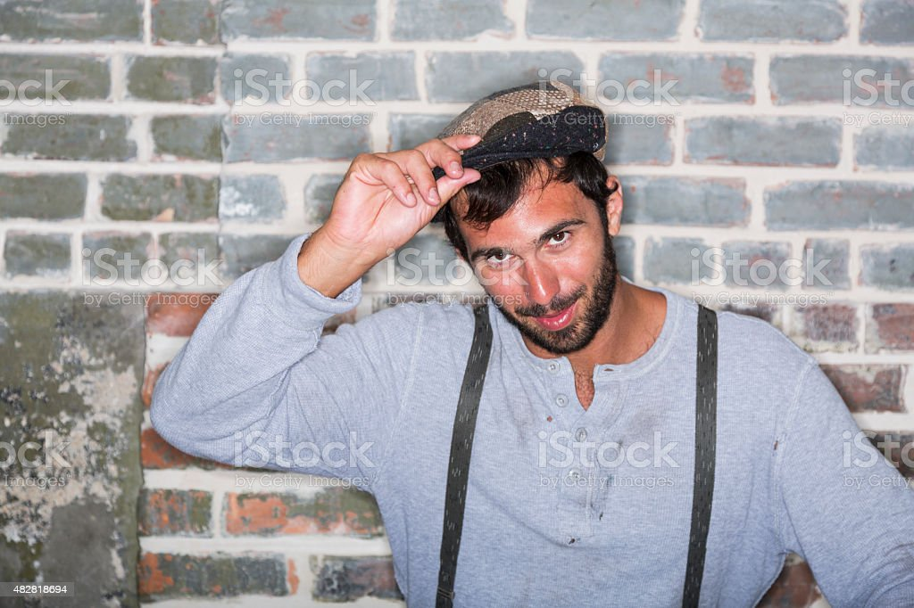 Portrait of man wearing suspenders tipping hat stock photo