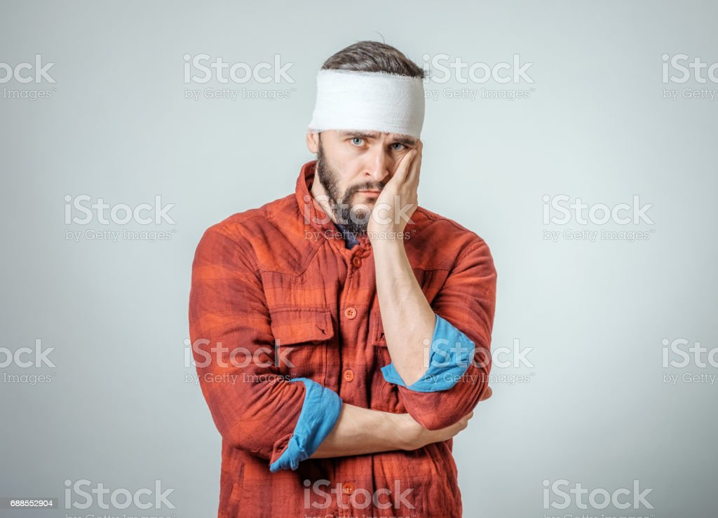 Portrait of man with bandages wrapped around his head isolated on...