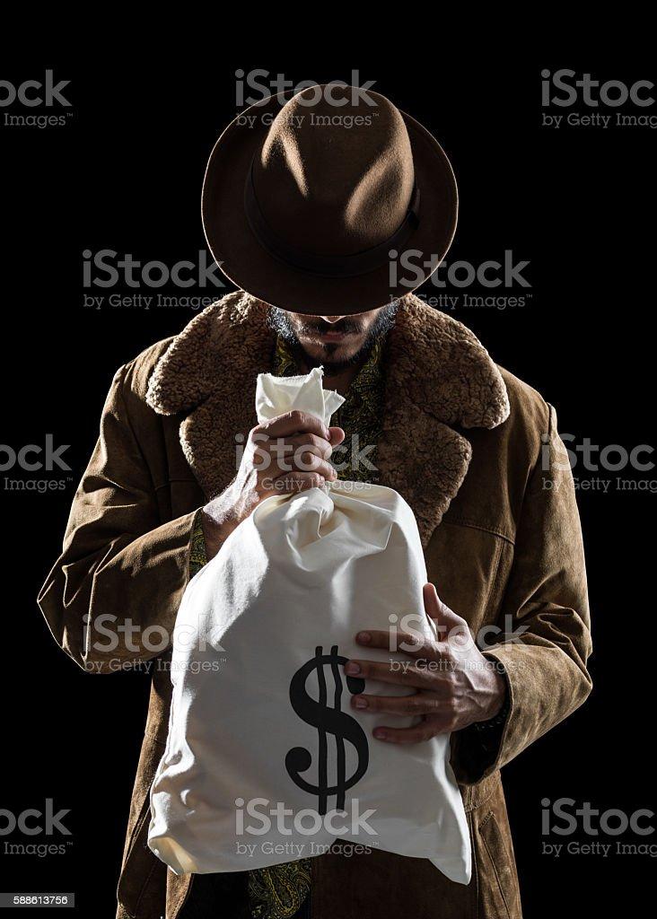 Portrait Of Man With Fedora Hat Holding Money Bag stock photo