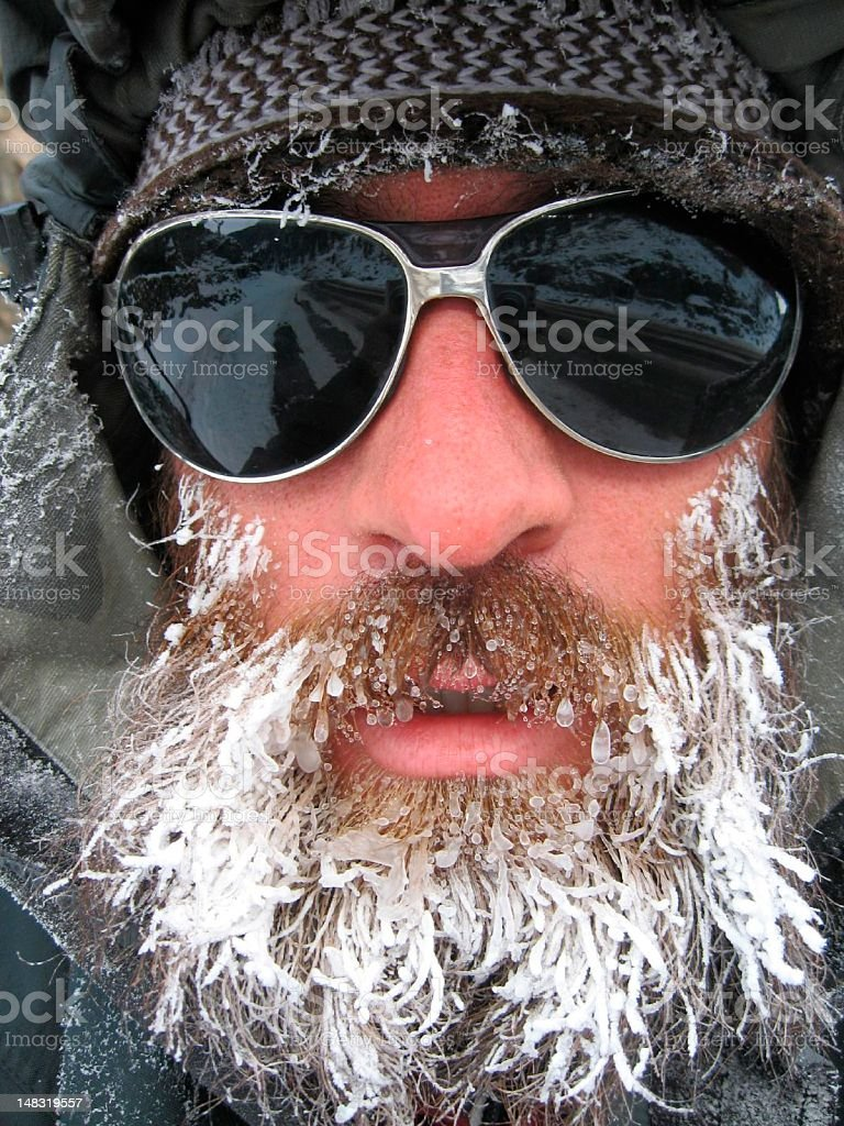 Portrait of man with frozen beard and sunglasses stock photo
