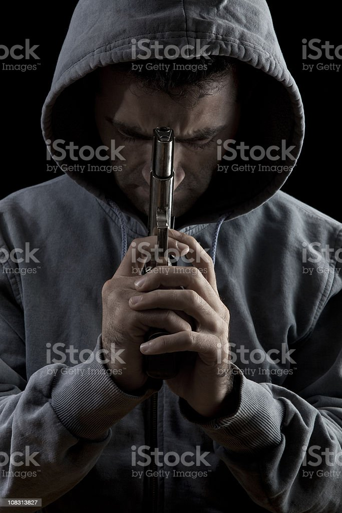 Portrait Of Man With Hood Holding Gun royalty-free stock photo
