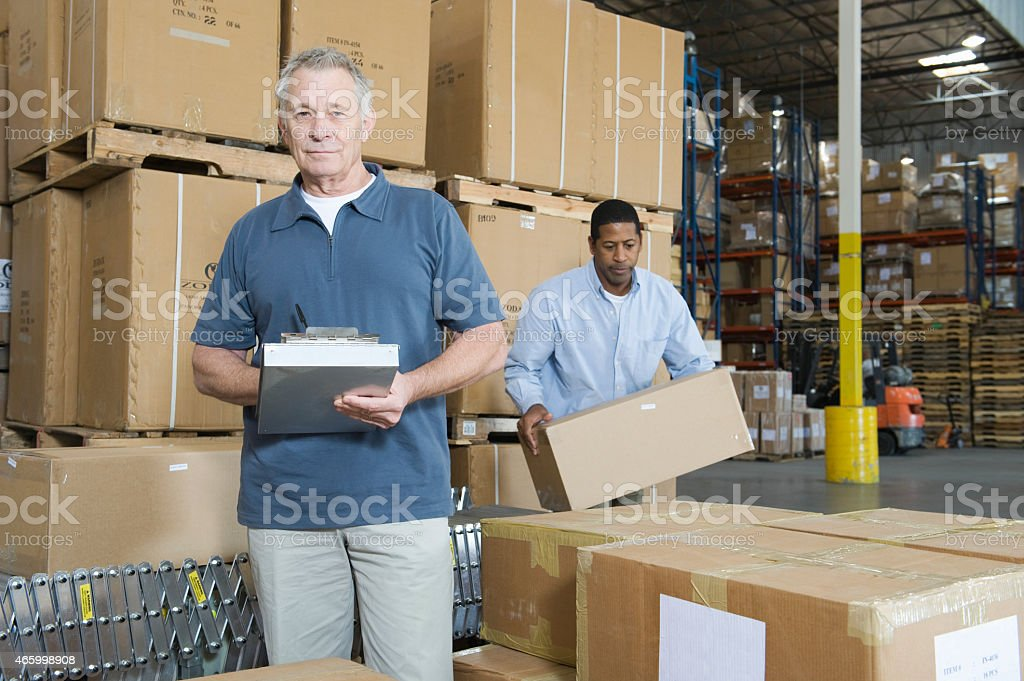 Portrait Of Man With Worker Behind At Warehouse stock photo