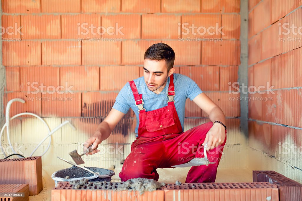 portrait of mason working and building brick walls. Industrial, stock photo