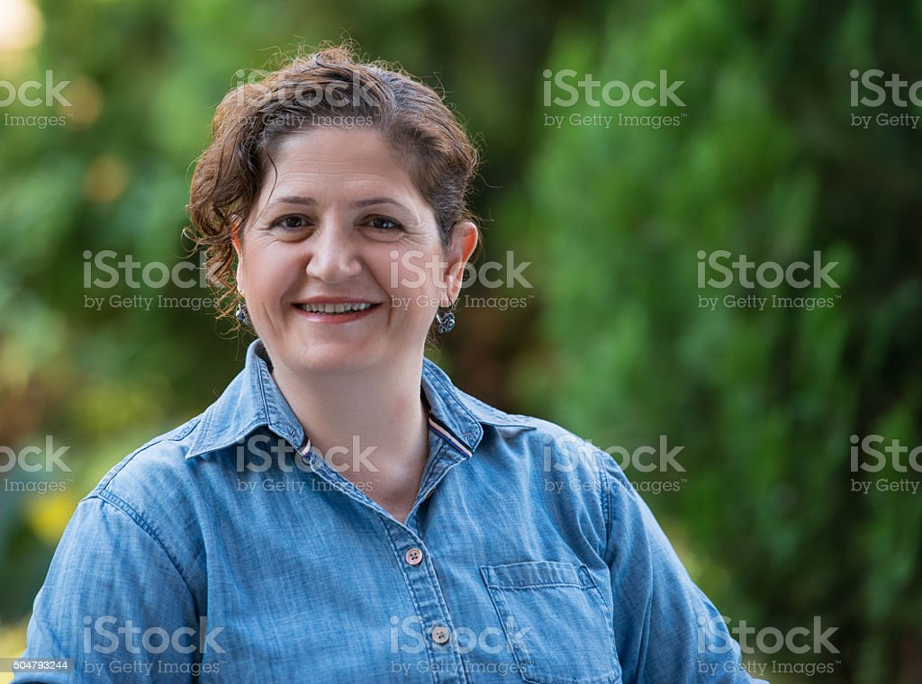 Portrait of mature adult female smiling to camera stock photo