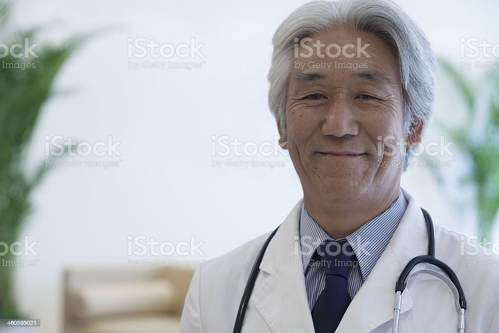 Portrait of mature doctor looking at camera and smiling stock photo