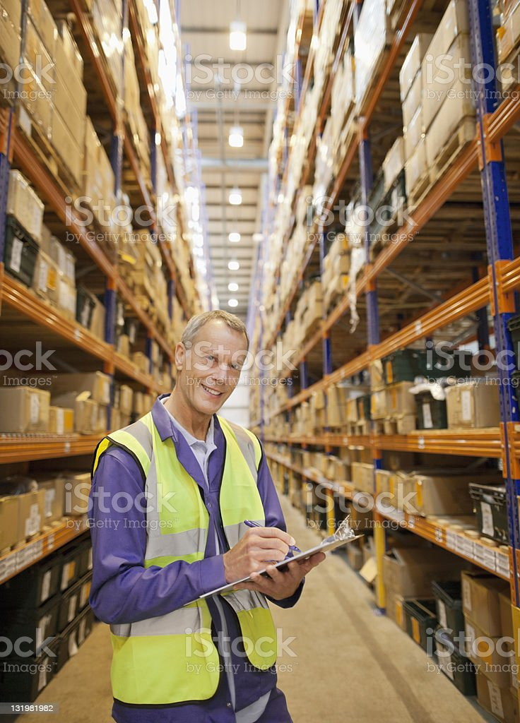Portrait of mature men examining boxes in warehouse stock photo