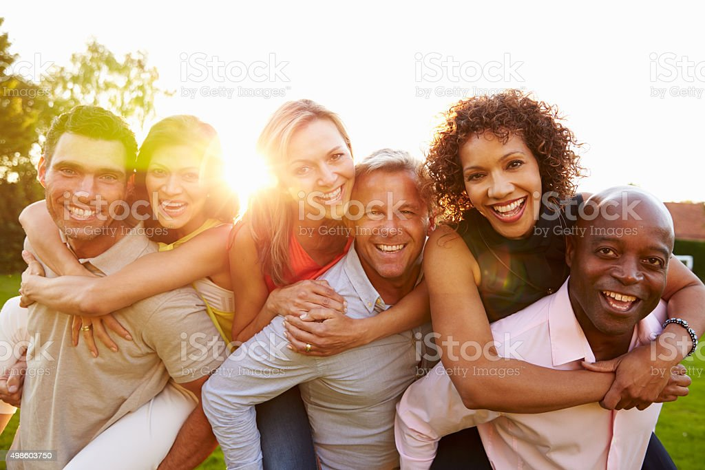 Portrait Of Mature Men Giving Women Piggy Backs stock photo