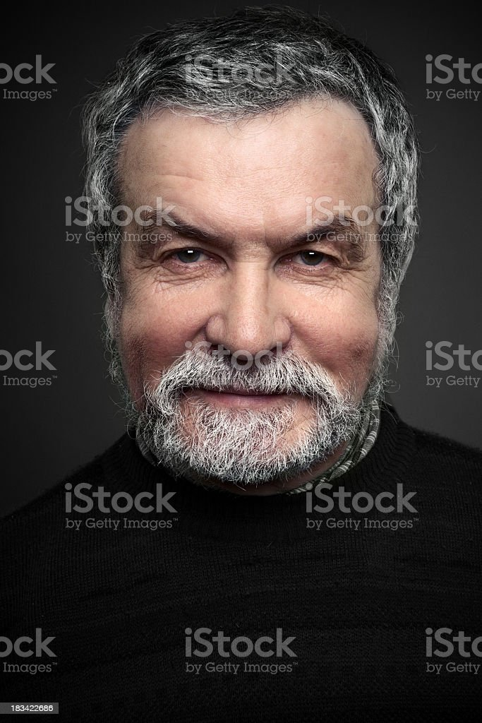 Portrait of mature smiling man on black background stock photo