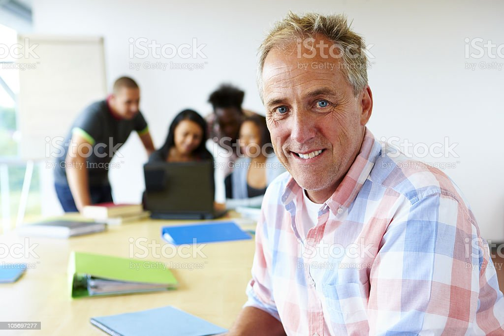 portrait of mature teacher with students behind royalty-free stock photo