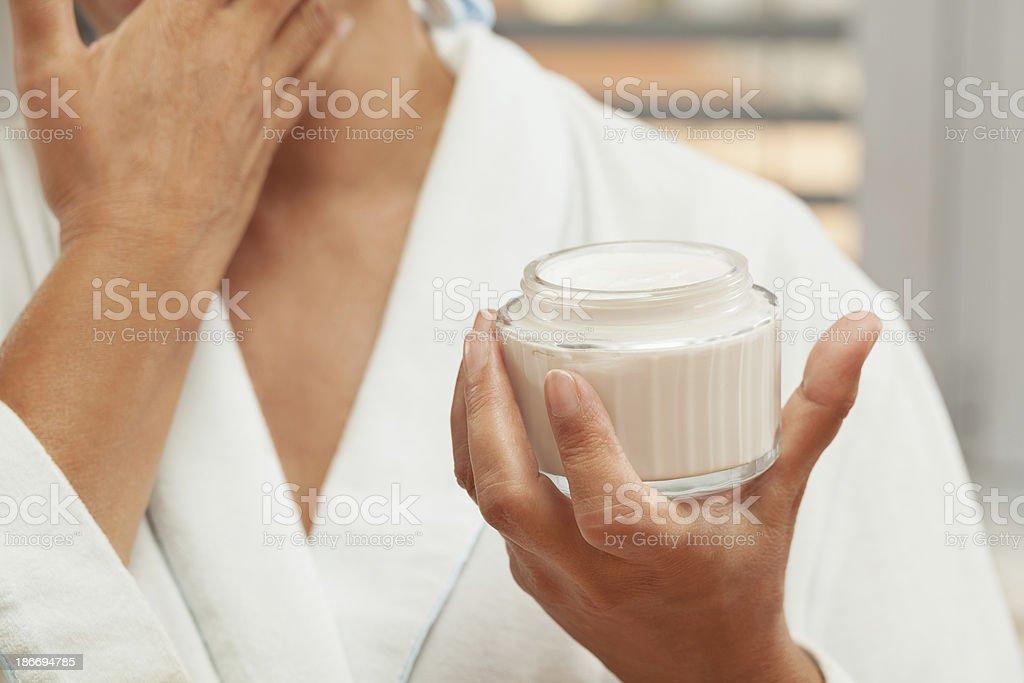 Portrait of mature woman applying facial cream royalty-free stock photo