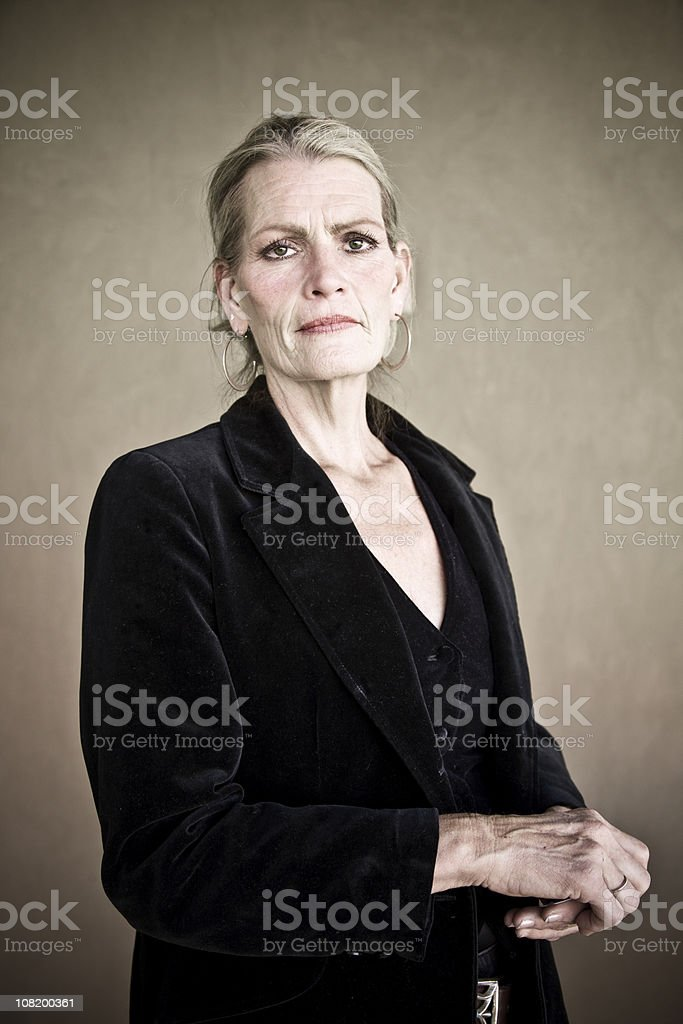 Portrait of Mature Woman on Brown Background royalty-free stock photo