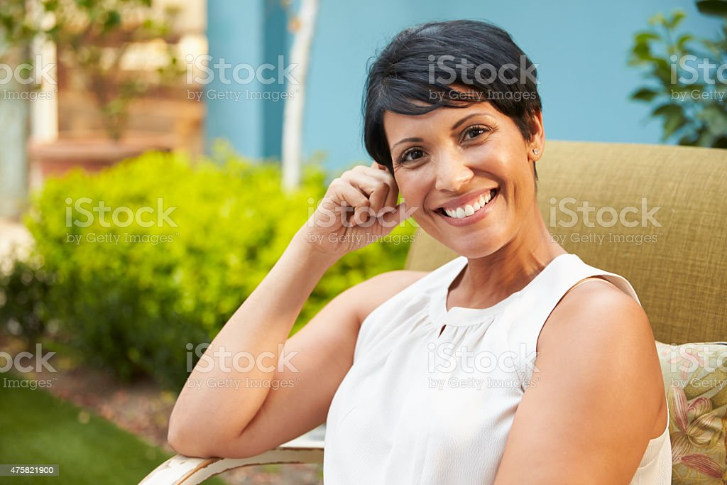 Portrait Of Mature Woman Relaxing Outdoors In Garden stock photo