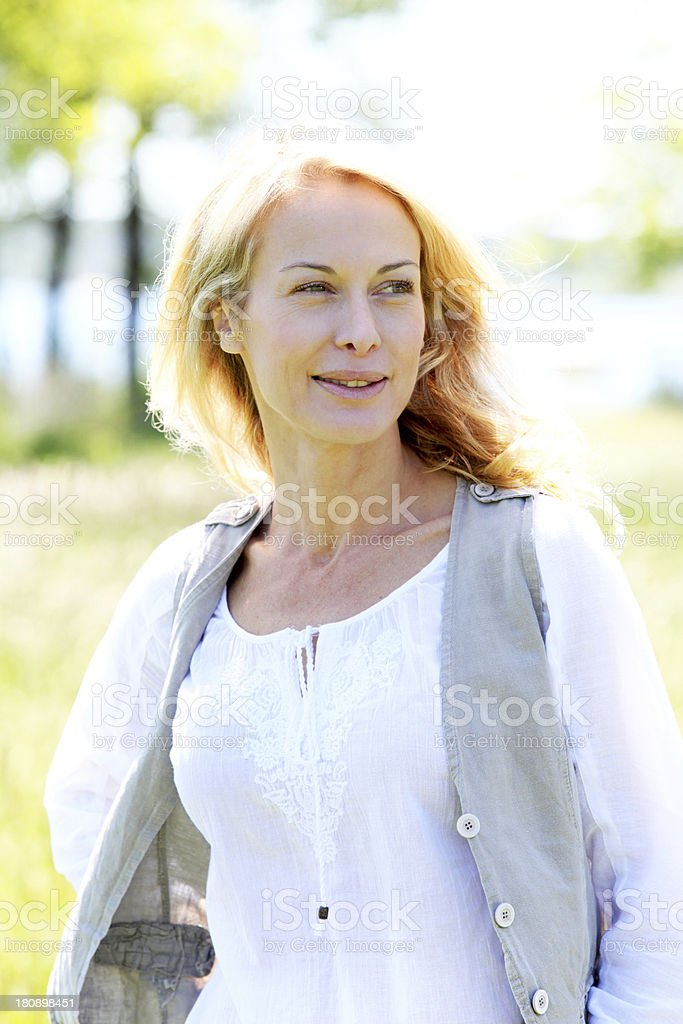 Portrait of mature woman walking in meadow on sunny day royalty-free stock photo