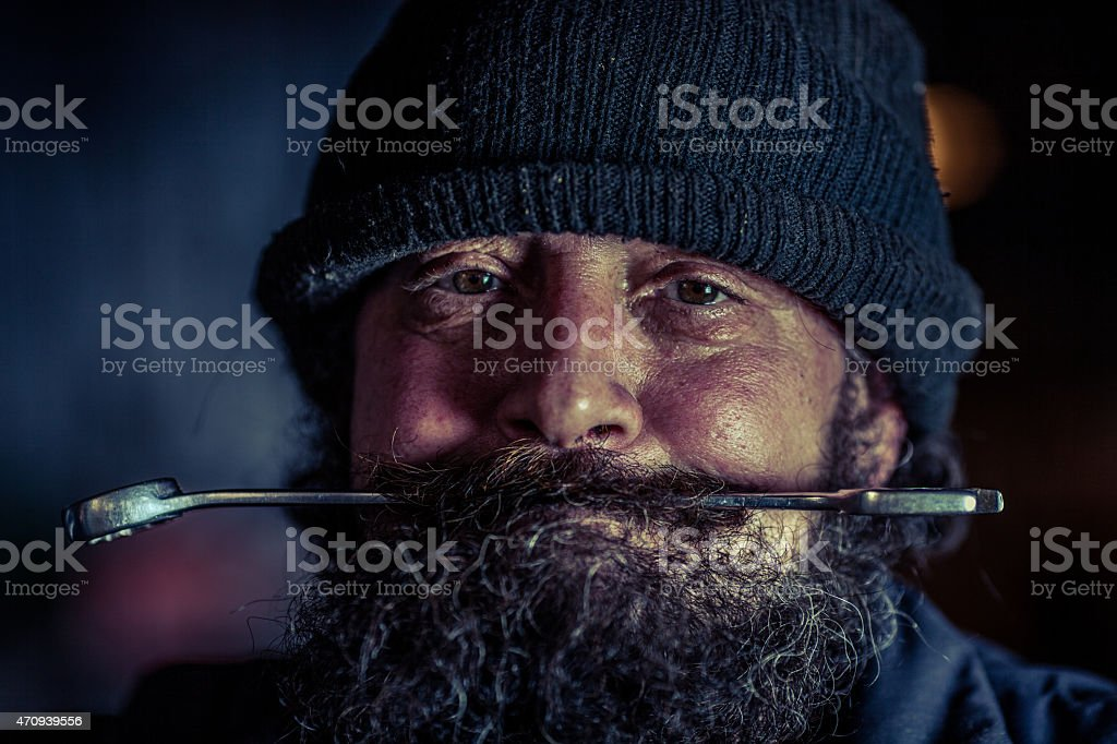 Portrait of mechanic with beard holding steel wrench in mouth stock photo