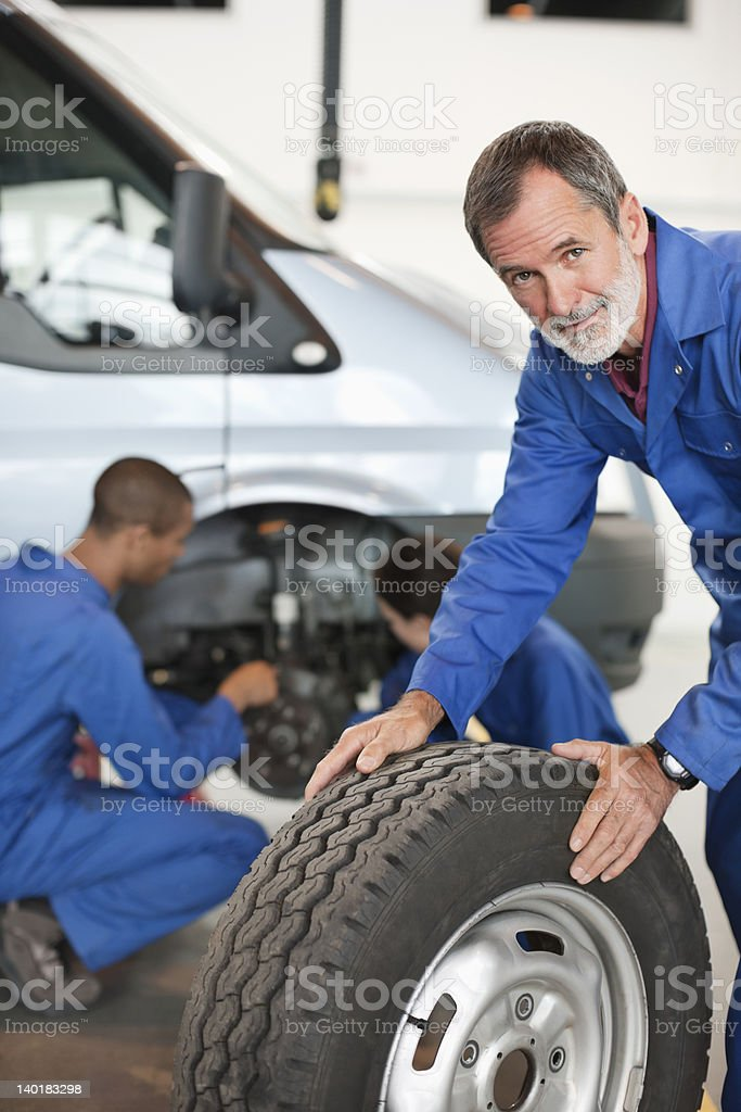 Portrait of mechanic with tire in auto repair shop royalty-free stock photo