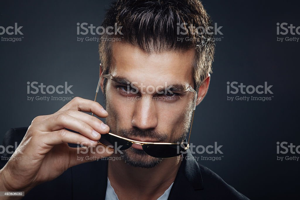 Portrait of men with sunglasses in hand stock photo